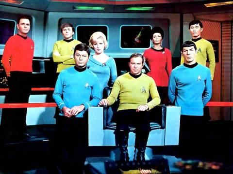 Uniforme clássico, com camisas em três cores, calças capri e botinas para os homens, e vestido para os mulheres.