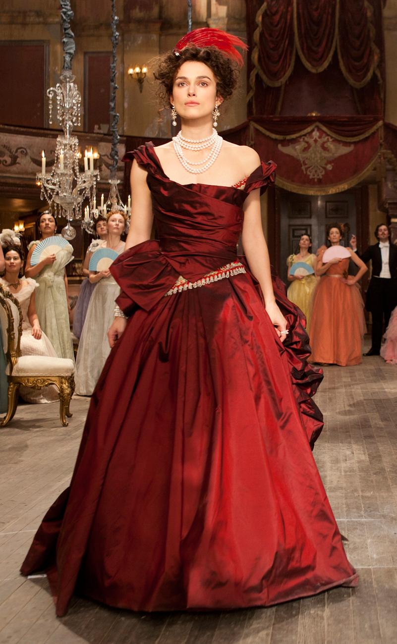 Vestido em cor vinho, com detalhes assimétricos no corpete e saia e com anquinha que se desmancha em drapeado